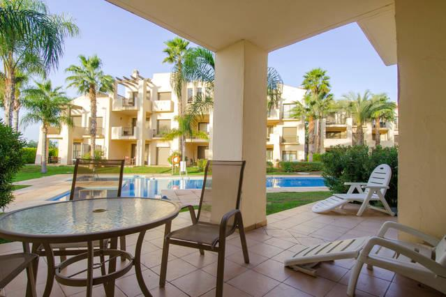 Spacious patio furnished with sunbeds, table chair and umbrella. half a dozen steps from the pool.