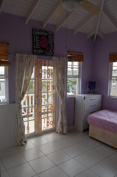 This bedroom leads out to an upstairs balcony that overlooks the garden and pool