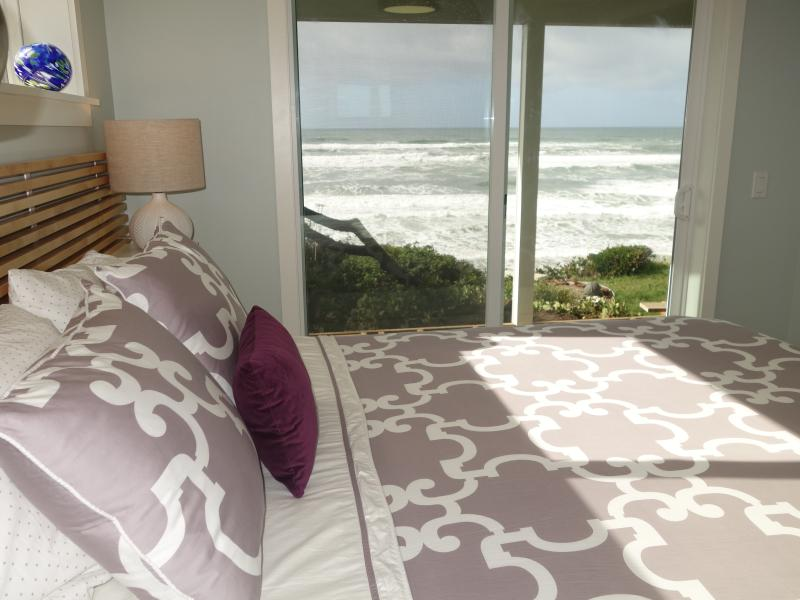Ocean view bedroom with queen bed and sliding glass door opening onto deck.