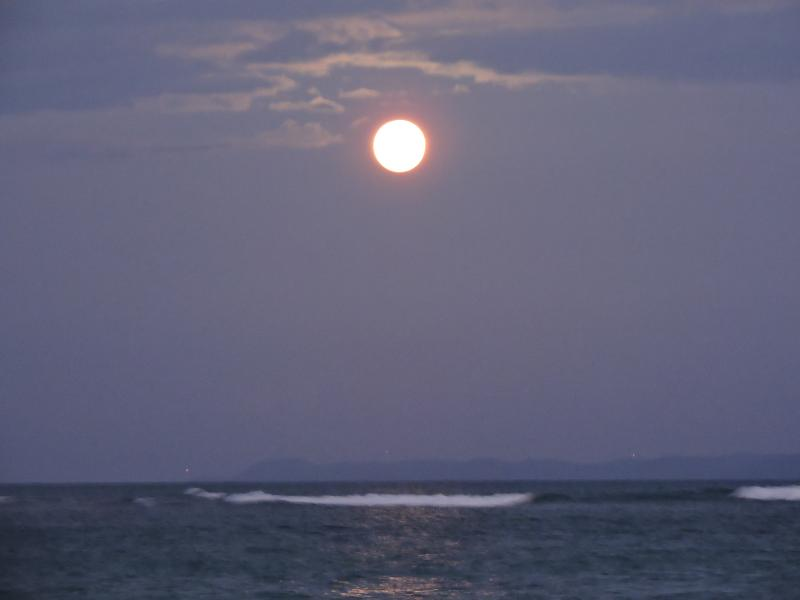 moon rising over ocean from the beach