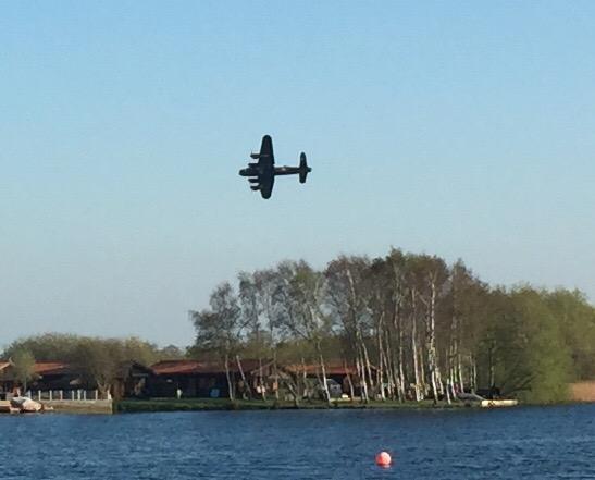 Lancaster flying over waterski lake cabins