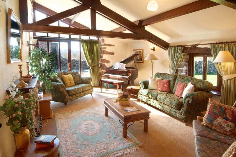 Wastwater light and spacious living area with antique baby grand piano