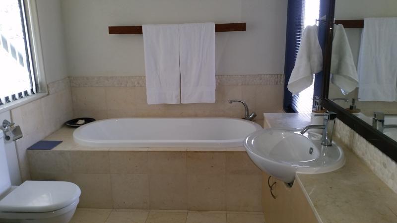 bathroom with a bath, shower, toilet