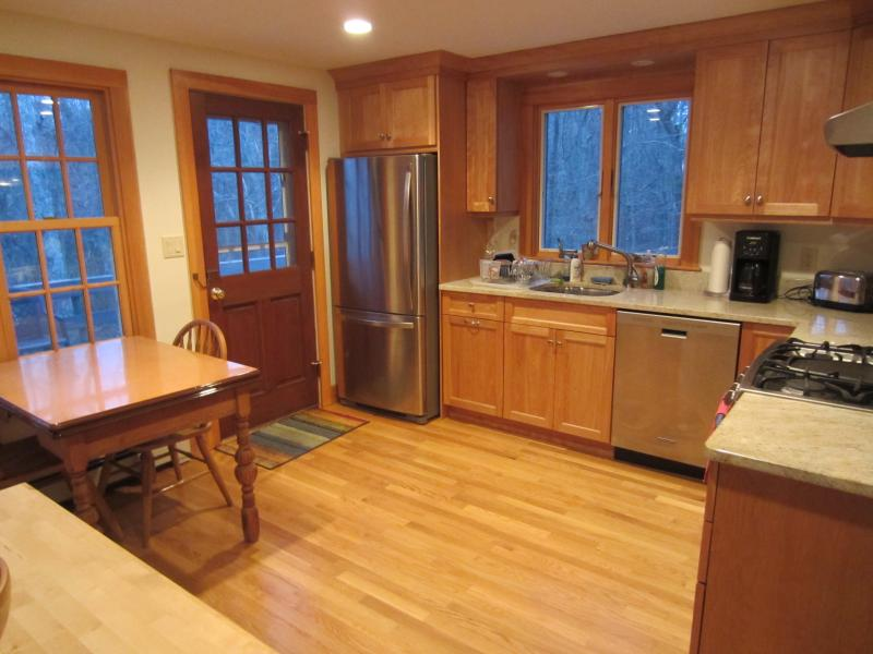 Shiny kitchen with granite counters with Beebe Woods out the window.