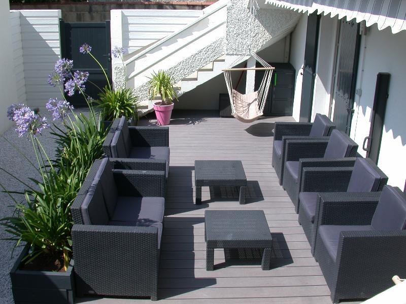 Terrasse avec salon de jardin et store banne dans cour close.