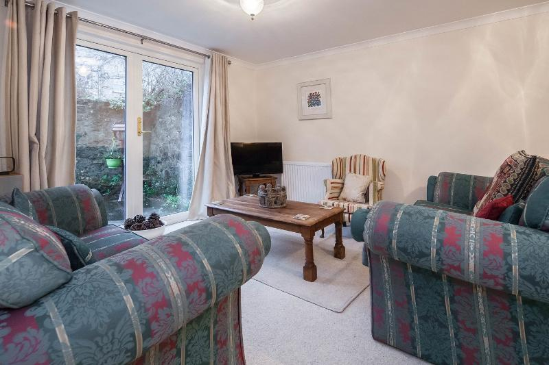 Spacious lounge with free Wi-Fi and patio doors leading to a fully enclosed courtyard garden