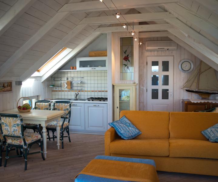 Cucina atrezzata, tavolo e sedie, divano letto e pouff letto in zona giorno Biancaneve