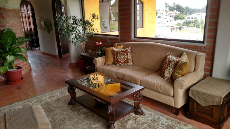 Enjoy a cozy living room with comfy seating, fireplace, veranda, lots of plants.