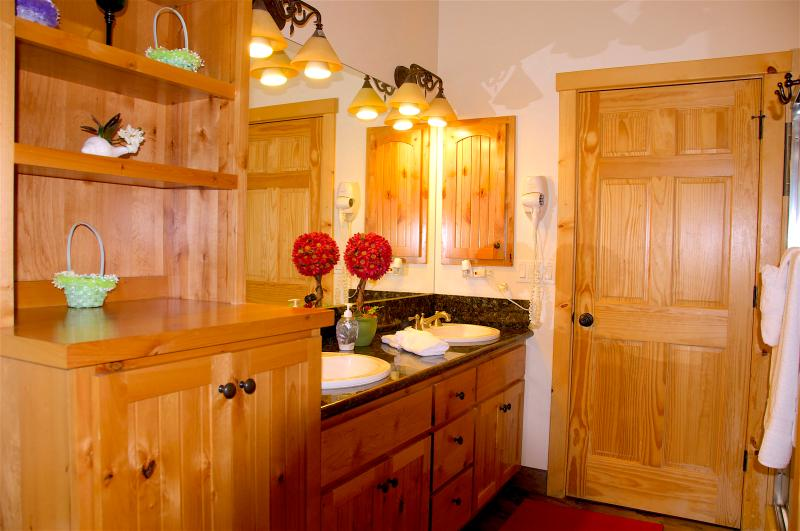 Bathroom in Hallway with Hickory Accented Cabinets and gorgeous Granite Countertop