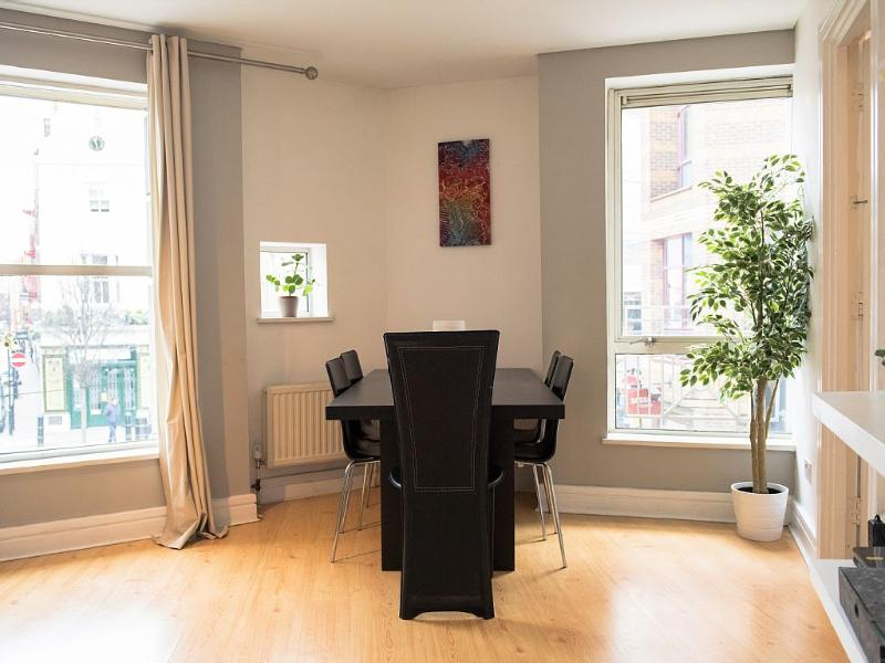 Large, solid dining table and chairs for 5 people directly beside the kitchen