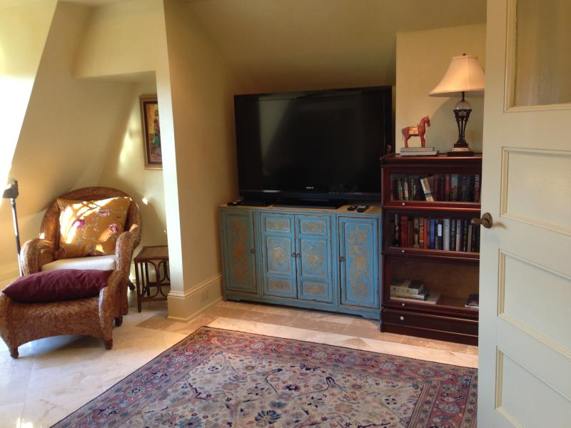 Large TV and reading chair in Les Reves, opposite the bed