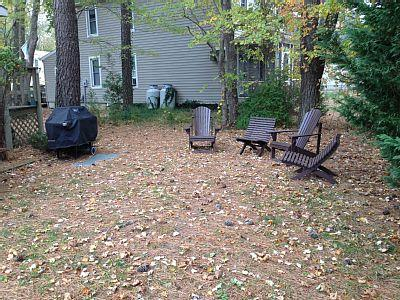 Gas grill and four Adirondack chairs.
