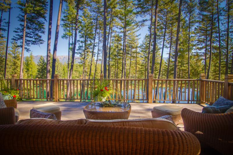 Large, lake and mountain view deck attached to house with shade or sun, gas grill, seating, tables