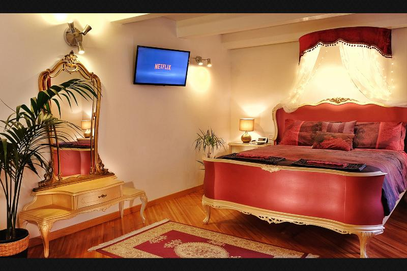 Luxury Royal Red Queen Bed in Gold finish with a Netflix powered TV and a Venetian Dresser.