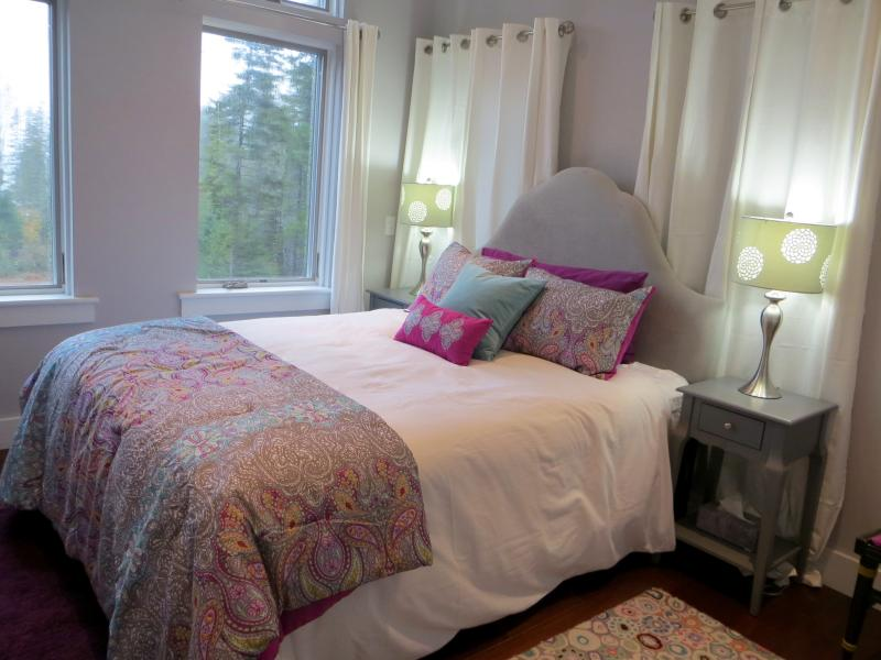 Light filled bedroom with luxurious upholstered queen bed, reading lamps, and bedside tables.
