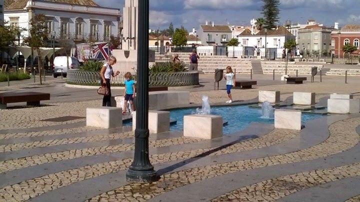 Kids playing in the fountain in the square at Tavira