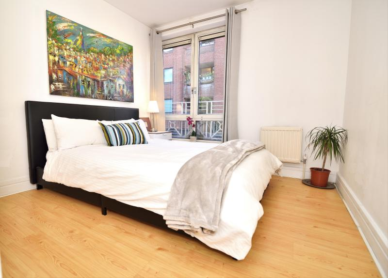 Master bedroom with large king size bed, and storage space. View of pedestrian street. Clean linens