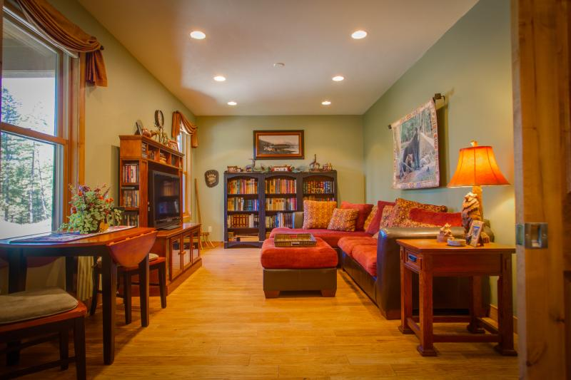 BEAR'S DEN themed media  room and library with sofa sectional queen fold out bed and privacy doors