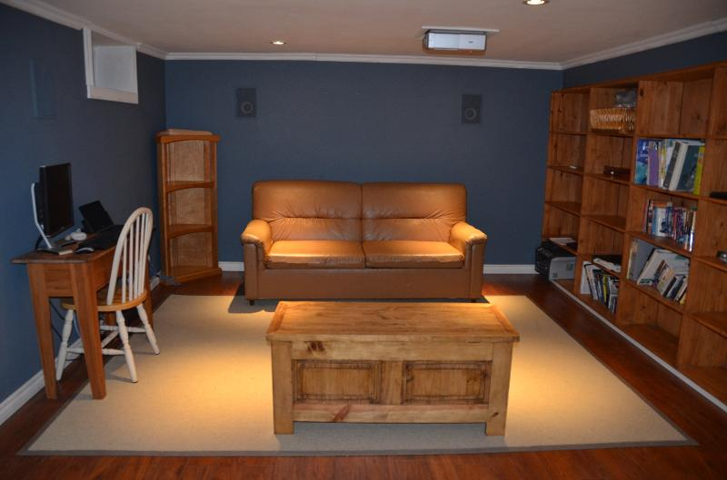 Home theatre with 92' screen and surround sound.
