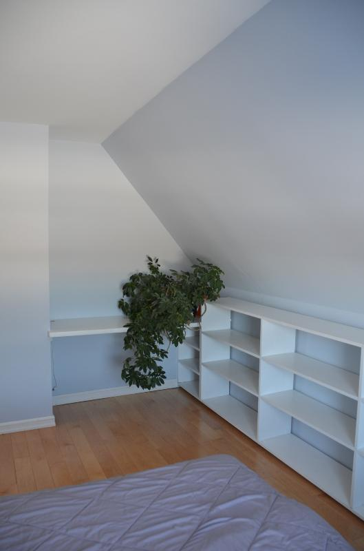 Third bedroom with double bed with custom shelves and desk.