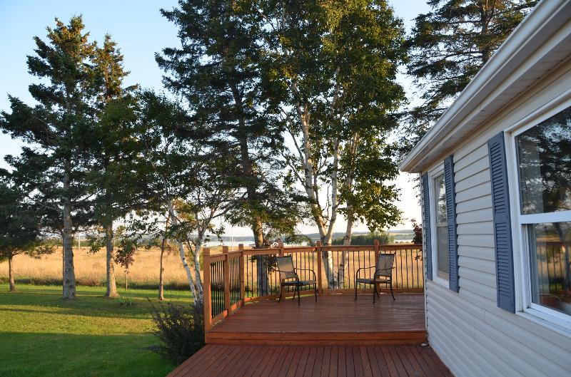Wrap around deck with the front half open and the side half a screened in porch.