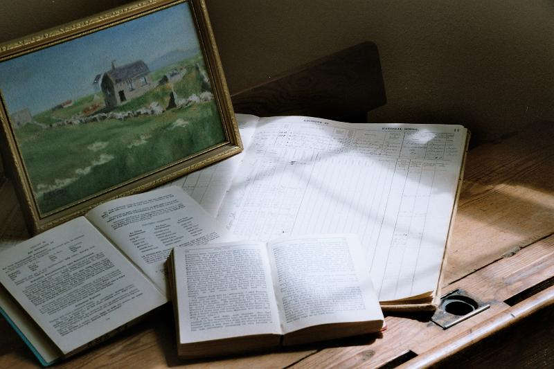 Artefacts include original fireplace, old school desks, pages from roll books, and school books.
