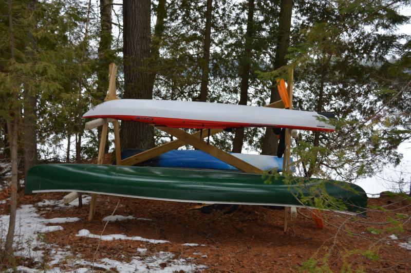 2 kayaks and a canoe, paddles, life preservers, lakeside.