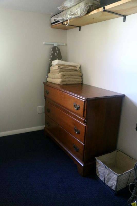 Ironing board, dresser and shelving. Hanging space for clothes not shown.