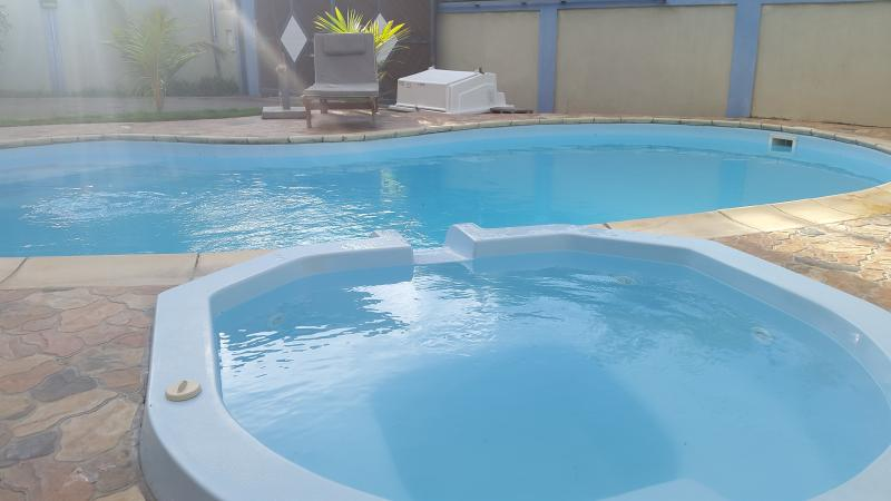 The swimming pool with attach jaccuzzi under the sun rays