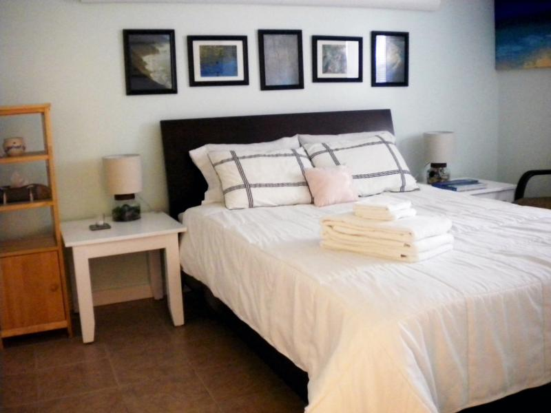 Newly Redesigned Queen Bedroom with Sea Foam paint, framed photos, new light fixtures and bedding