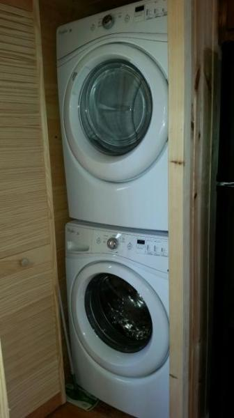 Double Washer and Dryer in cabin with laundry soap.