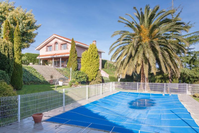 Vista de la casa mas jardín y piscina