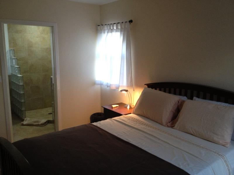 Bedroom with queen sized bed and ensuite shower.