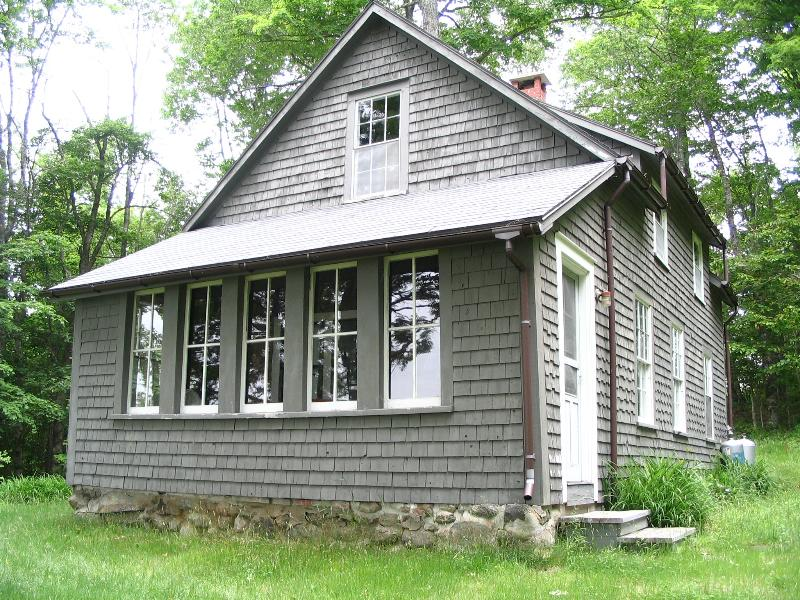 The front of Watercress Cottage with the trees and Boyden Lake reflecting in the porch windows
