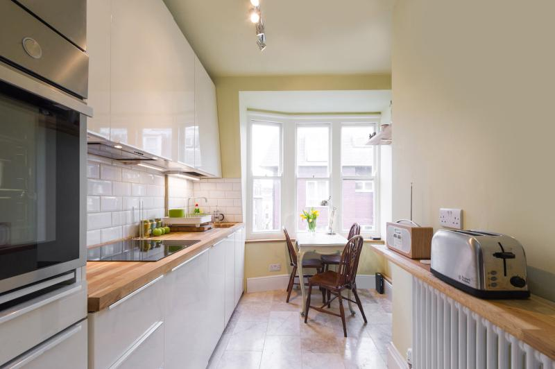 Fully-equipped kitchen with all modern appliances: fridge/freezer, induction hobs, built-in cooker.