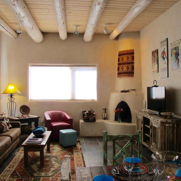 The living room features vigas and a kiva fireplace.