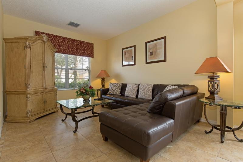 Large living area with comfortable leather sectional sofa and flat-screen TV