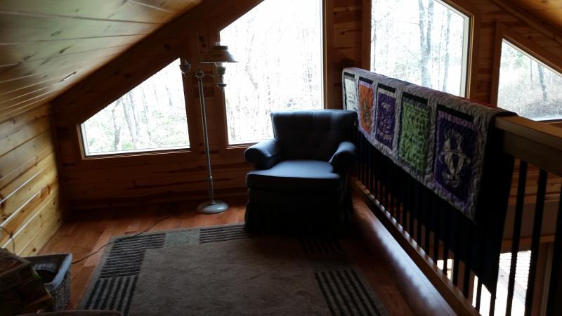 Loft zithoek met grote ramen aan de voorzijde van het huis.