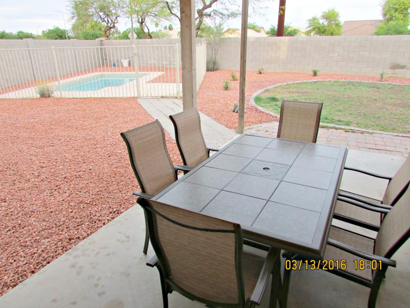 Backyard pool area with outdoor patio seating for 6