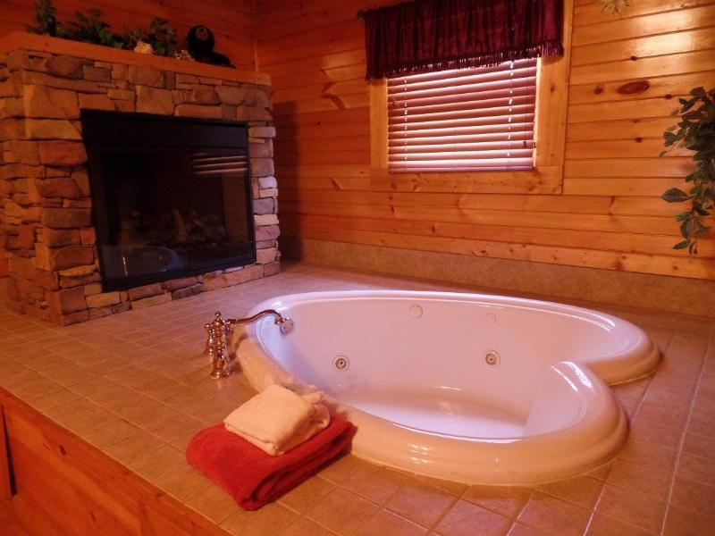 Relax in heart-shaped Jacuzzi while enjoying the romantic fireplace