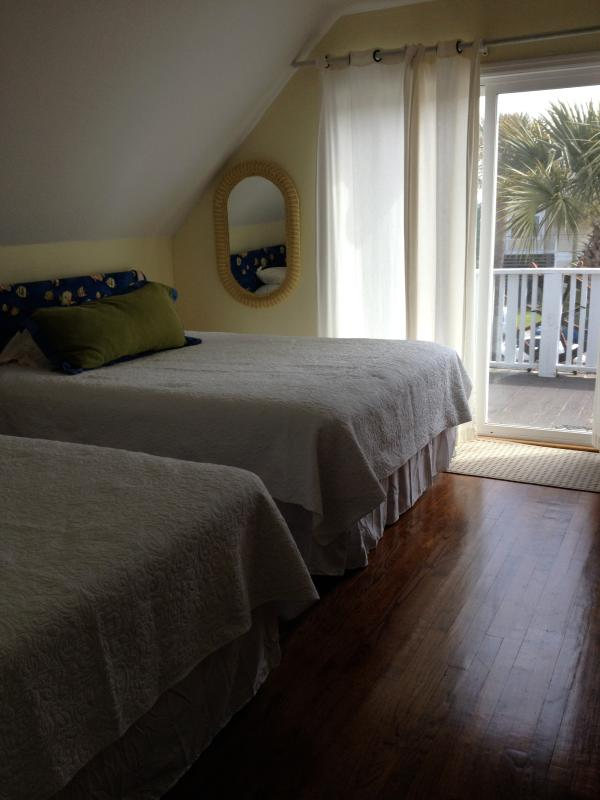 3rd Floor bedroom with 2 queen size beds. The deck outside looks out toward the ocean.