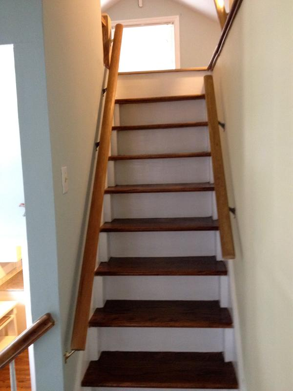 Stairs to a small children's loft that has 2 full size mattresses on a carpeted floor. Ceiling is 4'