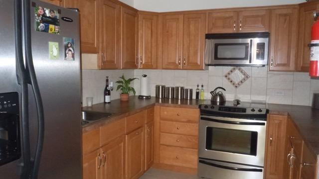 Modern kitchen with a full size fridge and stove. It also has a microwave, coffee pot and tea kettle