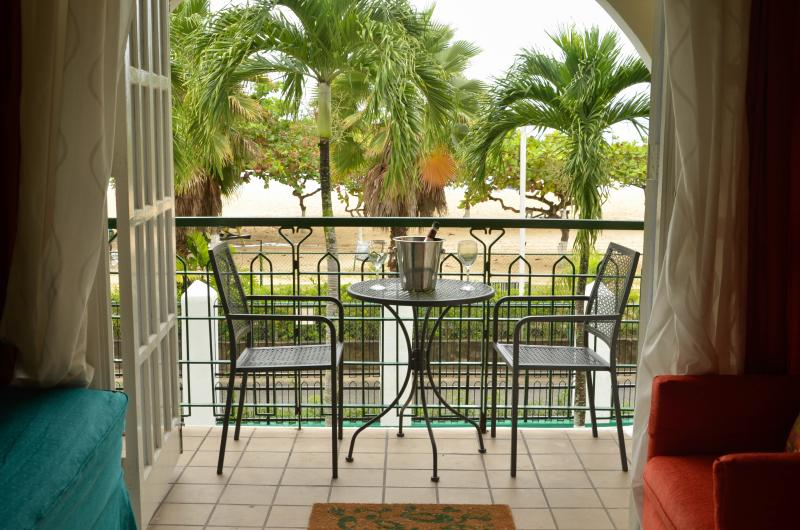 Enjoy a drink on Serenity's covered balcony looking out to the gardens and the Caribbean sea