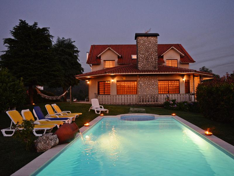 Vivenda e piscina iluminada à noite