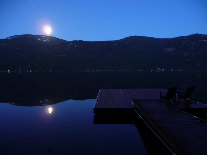 As the Moon's mirror image begins to fade over the mountain, a new day begins.