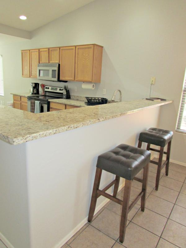 Kitchen w/ granite counter tops and bar style seating