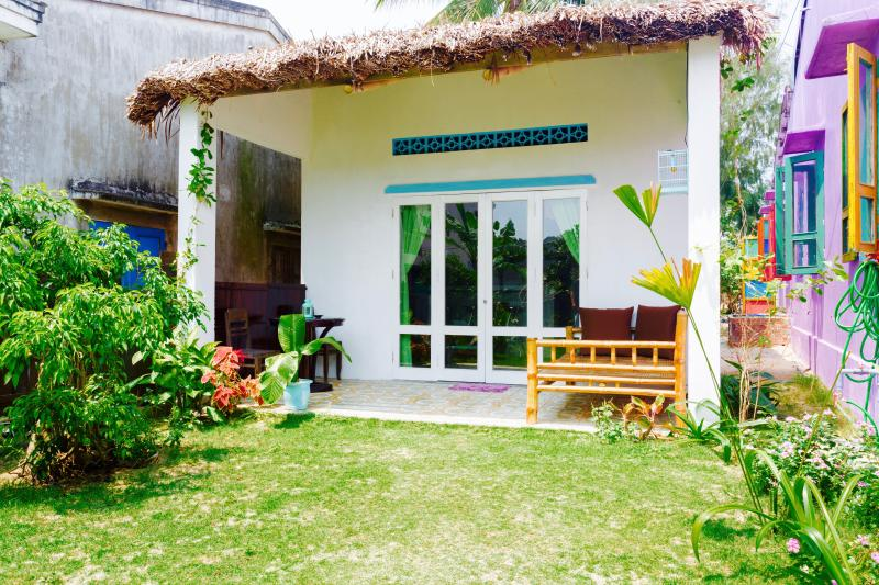 The cute private house with a coconut leaf roof, a terrace, an outdoor bed and a big entry door...