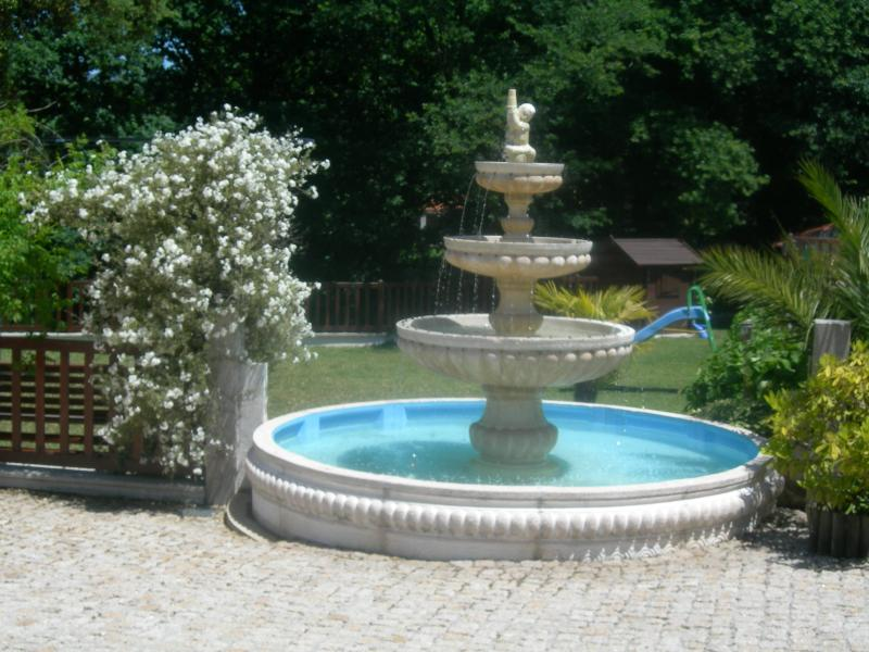 Fountain with family garden behind (slide no longer present) with child's garden play house.