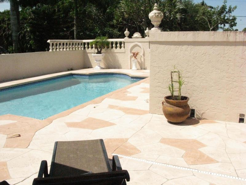 privacy with wall around pool area. Outside the walled area is a garden with several fruit trees